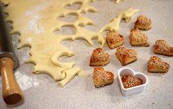 Cookies cozidas na forma da lareira e massa no fundo, no th Fotografia de Stock