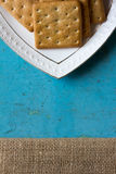 Cookies crackers in a white saucer on a blue background Stock Image