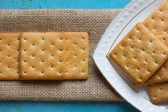 Cookies crackers in a white saucer and matting Royalty Free Stock Photography