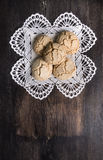 Cookies with cracks on  laced napkin  dark old desk Stock Photos