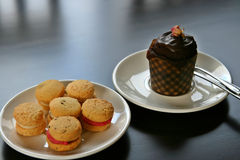 Cookies and cup cake. Afternoon tea with cream filled cookies and a chocolate cup cake Royalty Free Stock Photos