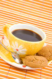 Cookies and cup with coffee. Close-up cookies and cup with cofee on bamboo table-cloth Royalty Free Stock Image