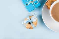 Cookies with cup of coffee and gift on blue, top view Royalty Free Stock Photography