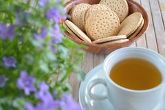 Cookies Cup of tea and Bellflowers on bamboo background Royalty Free Stock Images