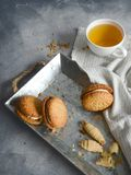 Cookies and cup of tea on iron plate stock image