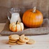 Cookies da abóbora na tabela de madeira com abóboras em um fundo Foto de Stock