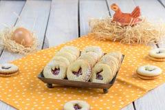 Cookies da Páscoa de Linzer com um doce de morango, espanado com açúcar a Fotografia de Stock