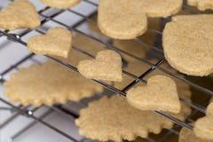Cookies de açúcar do coração do Valentim em prateleiras da cremalheira refrigerando em tamanhos diferentes fotografia de stock