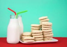 Cookies de açúcar empilhadas na placa com as duas garrafas do leite Fotografia de Stock Royalty Free