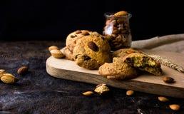Cookies de biscoito amanteigado americanas com gotas de chocolate e um jarro de leite e de amêndoas Fundo escuro do grunge Luz mí foto de stock royalty free
