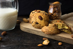 Cookies de biscoito amanteigado americanas com gotas de chocolate e um jarro de leite e de amêndoas Fundo escuro do grunge Luz mí fotos de stock