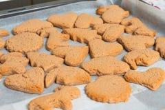 Cookies de cozimento frescas de formas diferentes em um close-up da folha de cozimento imagem de stock royalty free