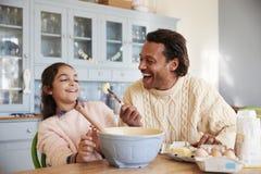 Cookies de And Daughter Baking do pai em casa junto fotos de stock royalty free