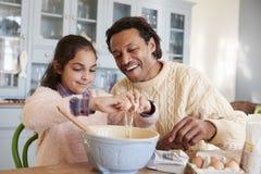 Cookies de And Daughter Baking do pai em casa junto imagens de stock