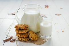 Cookies de farinha de aveia caseiros com passas e ameixas secas com jarro e vidro do leite no fundo de madeira branco Nenhum açúc foto de stock