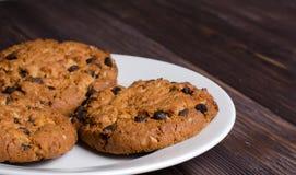 Cookies de farinha de aveia caseiros em uma placa branca Fundo de madeira fotografia de stock