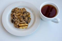 Cookies de farinha de aveia caseiros na placa com o tampão do chá no fundo branco imagem de stock