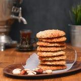 Cookies de farinha de aveia com porcas e chá no samovar em uma tabela de madeira foto de stock royalty free