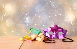 Cookies de Hamantaschen ou orelhas dos hamans, noisemaker e máscara para a celebração de Purim (feriado judaico) e fundo do brilh Imagens de Stock Royalty Free