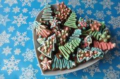 Cookies decoradas do mel do Natal no fundo do inverno com flocos de neve Fotos de Stock Royalty Free