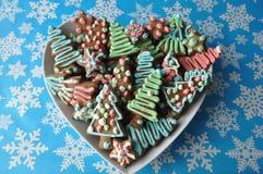 Cookies decoradas do mel do Natal no fundo do inverno com flocos de neve Imagens de Stock