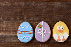 Cookies decorated as easter eggs and chick. A pile of some different handmade cookies patterned as decorated easter eggs and as a funny chick against a rustic Stock Images