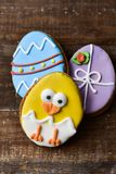 Cookies decorated as easter eggs and funny chick. High angle view of some homemade cookies decorated as ornamented easter eggs and a funny chick, on a rustic Royalty Free Stock Images