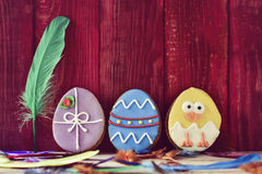 Cookies decorated as easter eggs. A pile of different some cookies patterned as different decorated easter eggs against a red wooden background, and feathers of Royalty Free Stock Image