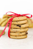 Cookies decorated with ribbons. A stack of freshly baked chocolate chip cookies decorated with a beautiful red ribbon. Focus is on the stack of cookies and falls Royalty Free Stock Photos