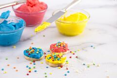 Free Cookies Decorated With Primary Colored Frosting With Rainbow Sprinkles Royalty Free Stock Photography - 172030317
