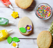 Cookies with decorations tools – icing, marzipan flower, nonpa Royalty Free Stock Image