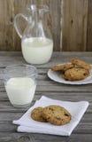 Cookies do chocolate e do arando com leite na tabela de madeira foto de stock royalty free