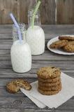 Cookies do chocolate e do arando com leite na tabela de madeira fotos de stock