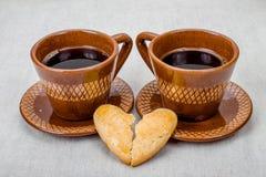 Cookies do coração quebrado e duas xícaras de café Fotografia de Stock