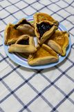 Cookies do doce do mirtilo e do abric? de Hamantash Purim na placa colorida na toalha de mesa com fundo azul dos quadrados imagem de stock