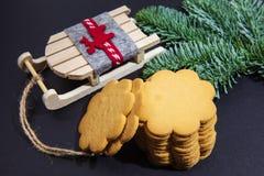 Cookies do gengibre, ramos do abeto e pequeno trenó de Santa Claus, em um fundo escuro imagem de stock royalty free