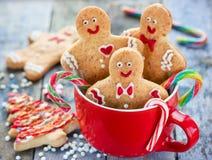 Cookies do homem de pão-de-espécie no copo vermelho, feriado do Natal que coze o CCB imagens de stock