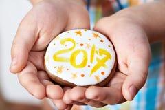 Cookies do Natal com número 2017 nas palmas da criança Foto de Stock