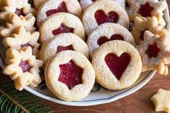 Cookies do Natal de Linzer em uma placa em uma tabela de madeira Fotografia de Stock Royalty Free