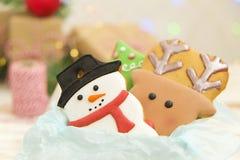 Cookies do Natal em uma caixa com presentes, luzes e ramos do abeto na tabela de madeira do vintage branco Efeito da neve, bokeh Foto de Stock Royalty Free