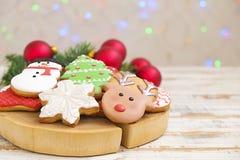 Cookies do Natal em uma caixa com presentes, luzes e ramos do abeto na tabela de madeira do vintage branco Efeito da neve, bokeh Foto de Stock