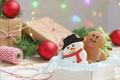 Cookies do Natal em uma caixa com presentes, luzes e ramos do abeto na tabela de madeira do vintage branco Efeito da neve, bokeh Imagens de Stock Royalty Free