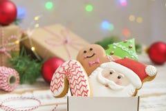 Cookies do Natal em uma caixa com presentes, luzes e ramos do abeto na tabela de madeira do vintage branco Efeito da neve, bokeh Fotos de Stock Royalty Free