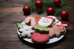Cookies do Natal na placa com ramo do abeto no fim de madeira do fundo acima Fotografia de Stock