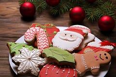 Cookies do Natal na placa com ramo do abeto no fim de madeira do fundo acima Imagens de Stock