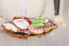 Cookies do pão-de-espécie do Natal na placa nas mãos do ` s das mulheres Imagens de Stock