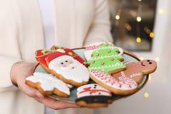 Cookies do pão-de-espécie do Natal na placa nas mãos do ` s das mulheres Fotografia de Stock Royalty Free