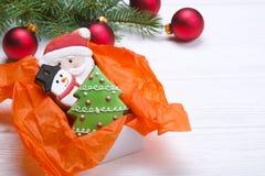 Cookies do pão-de-espécie do Natal no fim de madeira branco do fundo da caixa de presente acima Fotos de Stock