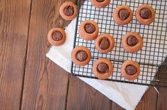 Cookies do thumbprint do ganache do chocolate em uma cremalheira de fio em um de madeira foto de stock royalty free