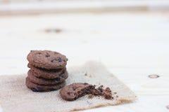 Cookies dos pedaços de chocolate com uma marca da mordida colocada em um saco em um wo fotos de stock royalty free
